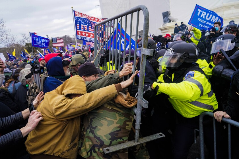 People push back against law enforcement using a metal fence as Trump flags wave