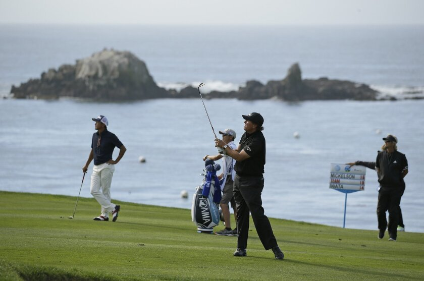 Phil Mickelson, foreground, follows his shot from the fourth fairway of the Pebble Beach Golf Links during the final round of the AT&T Pebble Beach National Pro-Am golf tournament Sunday, Feb. 14, 2016, in Pebble Beach, Calif. Hiroshi Iwata, of Japan, looks on. (AP Photo/Eric Risberg)