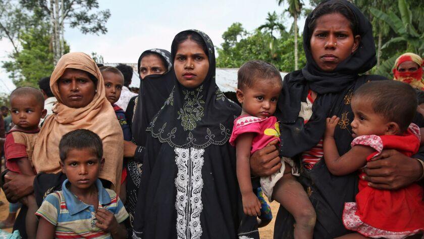 Members of Myanmar's Muslim Rohingya ethnic minority wait to enter the Kutupalong makeshift refugee