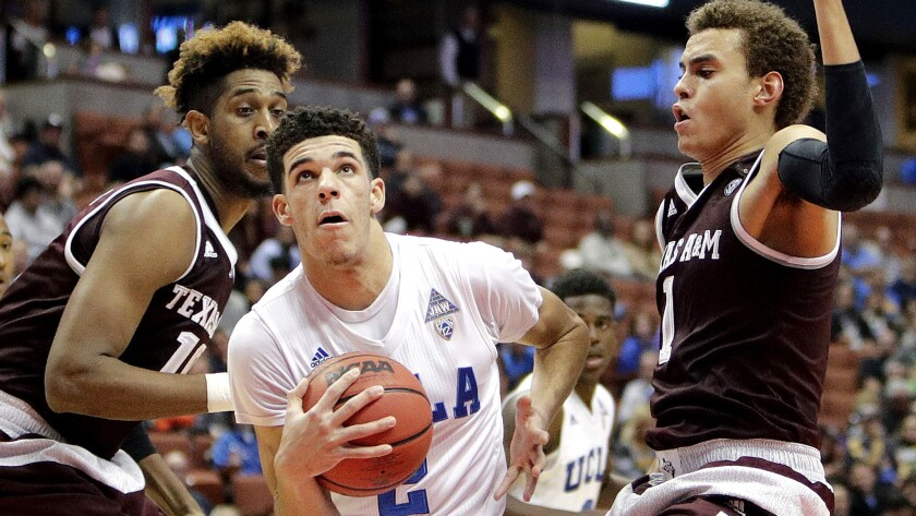 UCLA guard Lonzo Ball drives to the basket between Texas A&M's Tonny Trocha-Morelos, left, and D.J. Hogg during the second half of the championship game in the Wooden Legacy on Sunday.