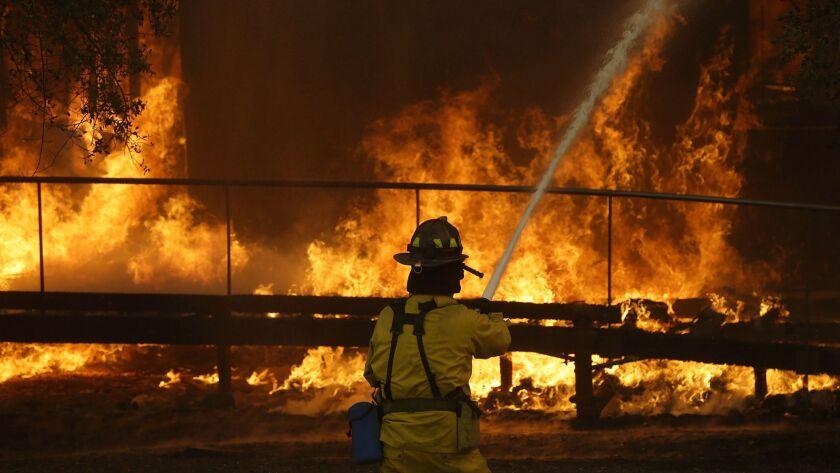 A firefighter battles flames spreading at a Keysight Technologies building in Santa Rosa, Calif.