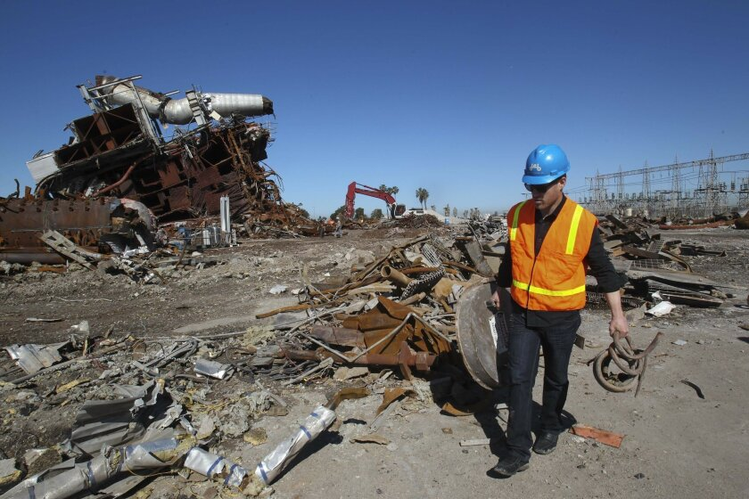 Michael Leaf carefully selects metal scraps in the aftermath of the South Bay Power Plant implosion in 2013.