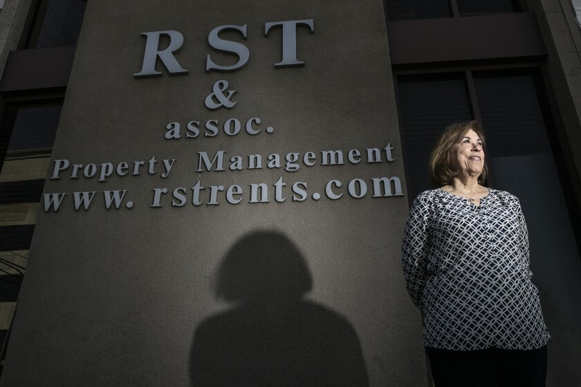 Irma Vargas stands in front of a sign for RST and Associates