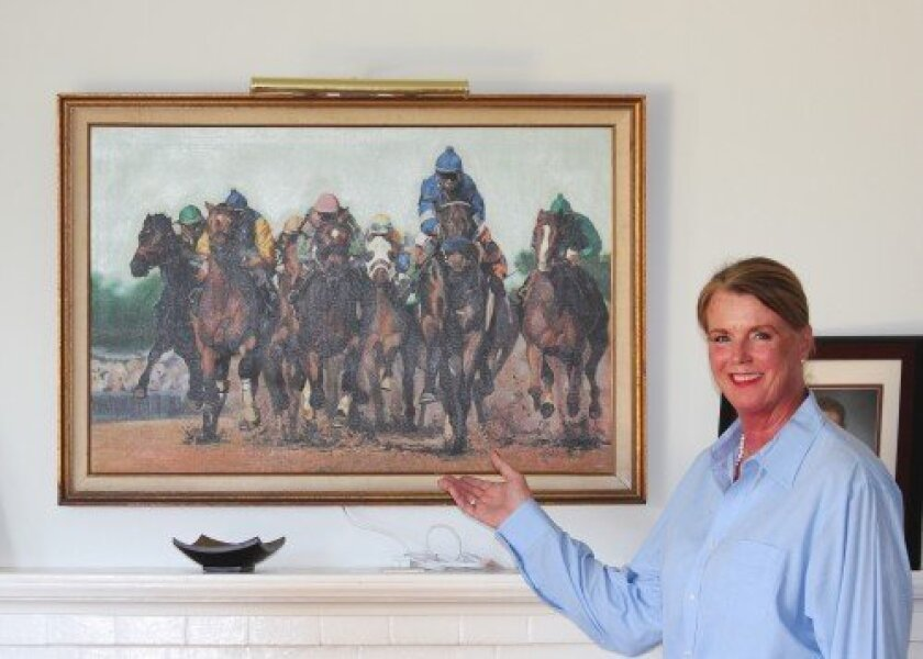Anne Waddell poses near a painting her husband purchased from her in the 1980s, so she could pay rent and remain in San Diego long enough for him to propose.