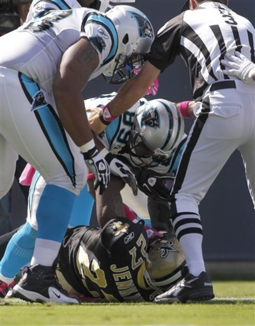 Players and officials try to separate Carolina Panthers' Steve Smith (89) and New Orleans Saints' Roman Harper (41) after Smith's touchdown during the first quarter of an NFL football game in Charlotte, N.C., Sunday, Oct. 9, 2011. (AP Photo/Bob Leverone)