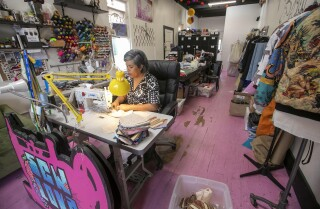 "Barrio Logan seamstress Claudia Rodriguez-Biezunski is making hand-made face masks from her sewing studio ""Sew Loka"" in Barrio Logan from instructions on the CDC website. On Monday morning, March 23, she was busily sewing the six pieces including the two elastic straps, in to completed masks. A crate with the mornings production sits at the side of her sewing machine."