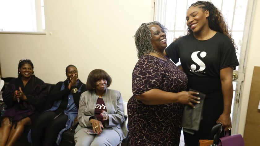 COMPTON, CA - NOVEMBER 30, 2018 - - Tennis great Serena Williams, right, receives a gift from Kandee