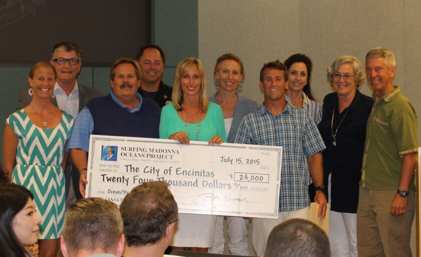 Encinitas city officials and members of the Surfing Madonna Oceans Project pose with a check for $24,000 donated to the city for ocean-related causes. Courtesy photo