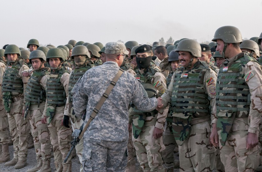 U.S. Staff Sgt. Kody Cross, center, congratulates Iraqi troops at their graduation from a six-week training course at Camp Taji, north of Baghdad. Questions persist about whether the struggling Iraqi military will be ready for an operation to retake Mosul from Islamic State militants.