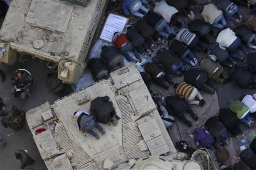 Anti-government protesters pray atop an Egyptian APC vehicle during traditional Muslim Friday prayers at the continuing demonstration in Tahrir Square in downtown Cairo, Egypt, Friday, Feb. 11, 2011. (AP Photo/Tara Todras-Whitehill)