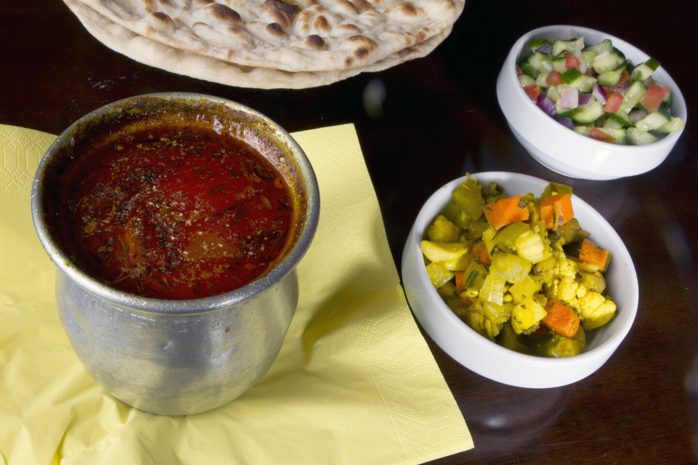 Dizi, left, a dish made with lamb meat, potato, tomato, turmeric and garbanzo and white beans baked in the oven for three hours, at Nersses Vanak Persian restaurant in Glendale.
