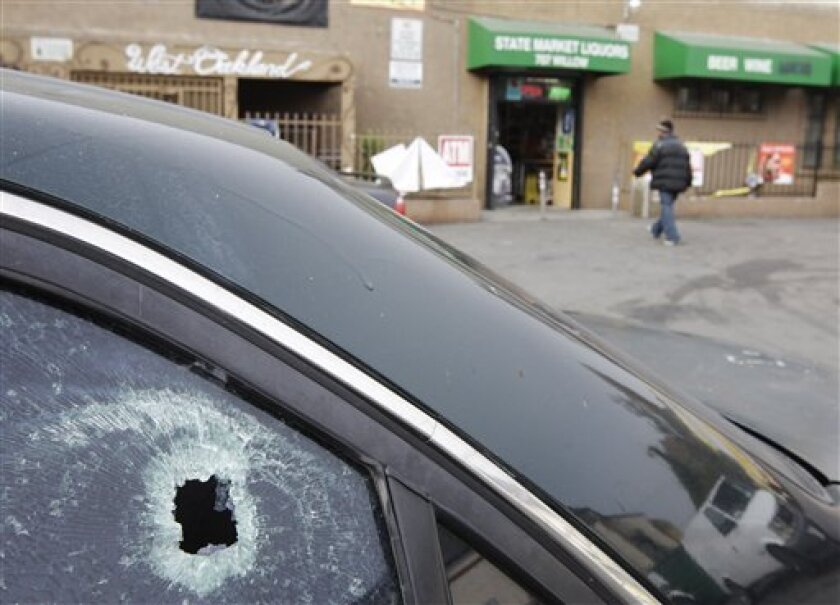 A bullet hole is shown in a window of a car at a liquor store parking lot in Oakland, Calif., Tuesday, Nov. 29, 2011 after a shooting. A hail of gunfire along an Oakland street left eight people wounded, including a 1-year-old boy and a woman who authorities say were hospitalized in critical condition. The gunfire broke out Monday evening in a liquor store parking lot after a crowd had gathered, police said. (AP Photo/Paul Sakuma)