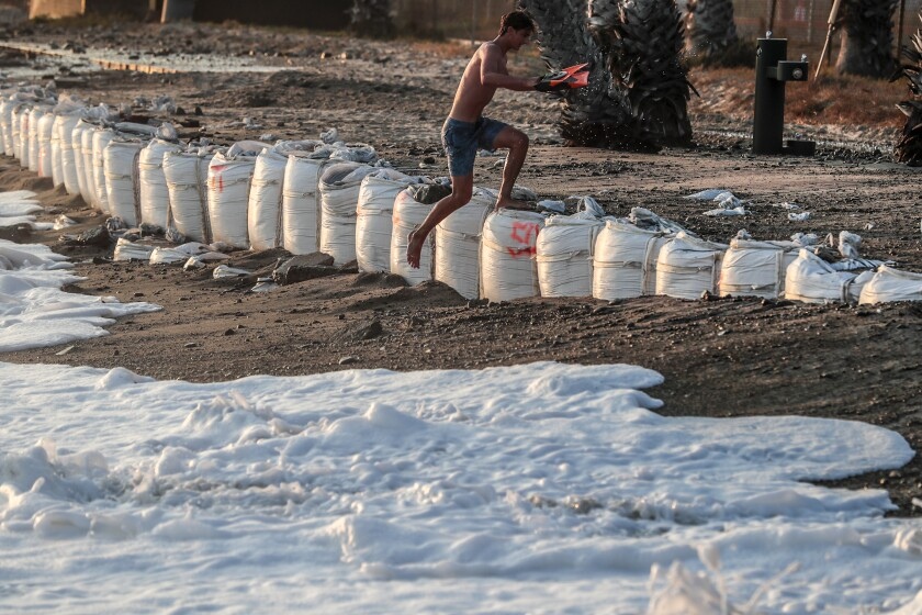 A swimmer jumps over white sandbags as the tide goes toward him at Capistrano Beach.