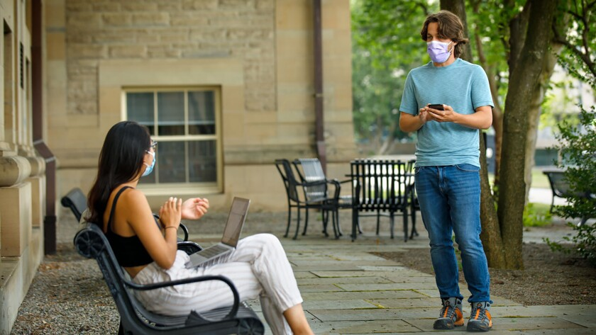 Bryan Maley, right, a graduate student at Cornell University, interviews a student about her mask-wearing experiences.