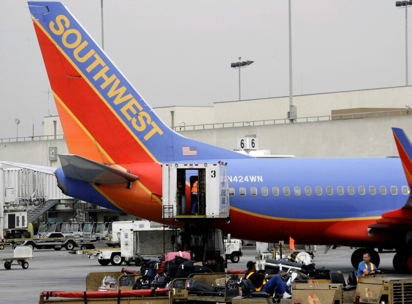 A Southwest Airlines plane is loaded with luggage at Los Angeles International Airport. Prosecutors announced Monday that three Southwest baggage handlers were among 14 people who circumvented airport security in order to smuggle drugs across the country.
