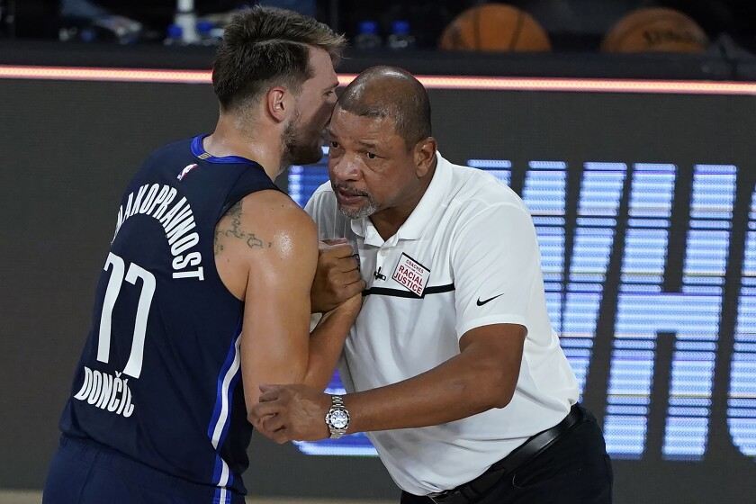 Dallas Mavericks star Luka Doncic speaks with Clippers coach Doc Rivers after a game on Aug. 6.