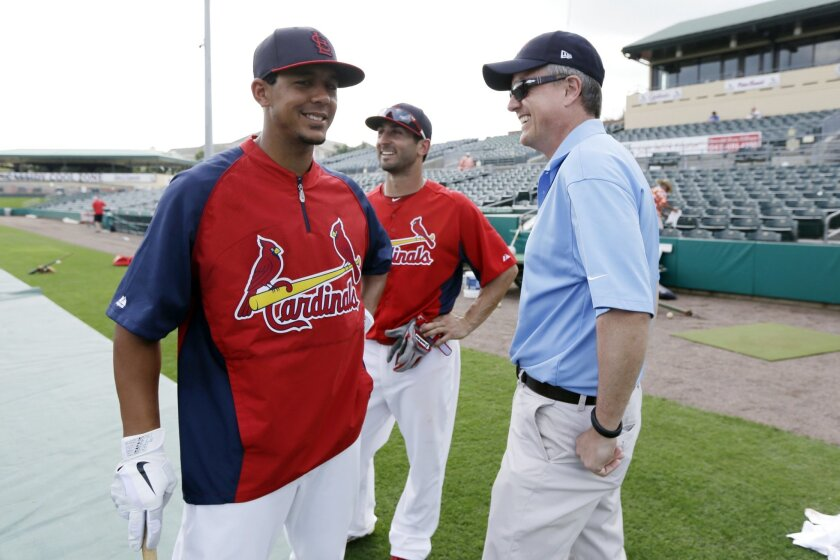 FILE - In this Feb. 25, 2013, file photo, Houston Astros general manager Jeff Luhnow, right, talks to St. Louis Cardinals center fielder Jon Jay, left, and second baseman Daniel Descalso before an exhibition spring training baseball game in Jupiter, Fla.  Major League Baseball says it is cooperatin