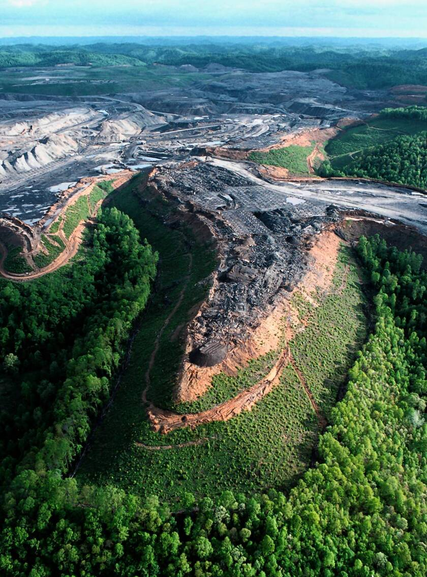 A coal mining operation in West Virginia where operators have blasted off a mountaintop to uncover valuable, low-sulphur coal seams. After the coal is removed, leftover rock and dirt is dumped into nearby valleys and streams.
