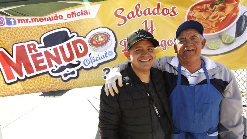 COMPTON, CA - MARCH 17, 2019 ? Roger Mendez, left, and his father Joel, with Mr. Menudo, sell menudo