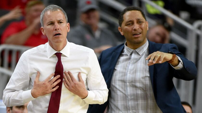 USC coach Andy Enfield, left, and associate head coach Tony Bland react to a play during a Pac-12 tournament game against UCLA on March 9, 2017, in Las Vegas.