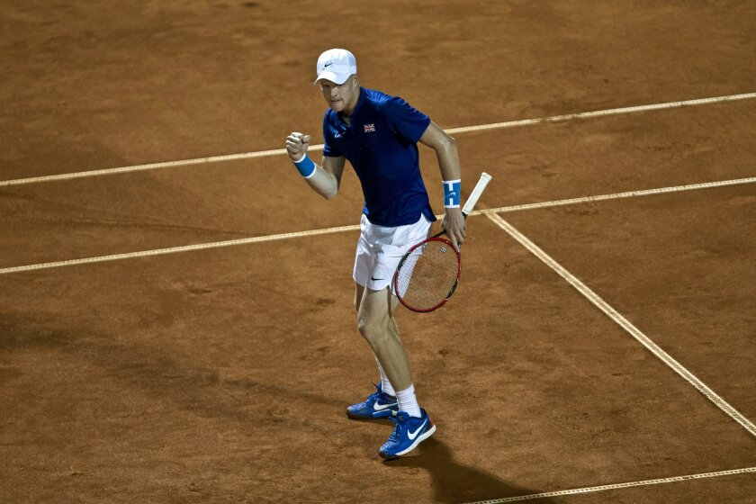 Britain's Kyle Edmund clenches his fist in celebration after winning a game against Serbia's Janko Tipsarevic during their Davis Cup quarterfinal tennis match in Belgrade, Serbia, Friday, July 15, 2016. (AP Photo/Marko Drobnjakovic)