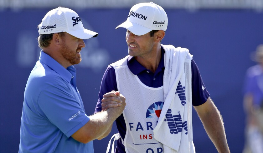 J.B.Holmes is congratulated by his caddie Brandan Parsons after getting a birdie at No. 18 to close the third round of the Farmers Insurance Open on Saturday at Torrey Pines.