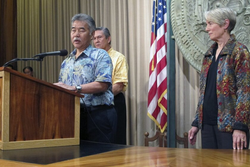 Hawaii Gov. David Ige, left, talks to reporters about the state's plans for fighting mosquito-borne illness as George Szigeti, president and CEO of the Hawaii Tourism Authority, center, and Virginia Pressler, director of the state Department of Health, listen on Friday, Feb. 12, 2016 in Honolulu. I