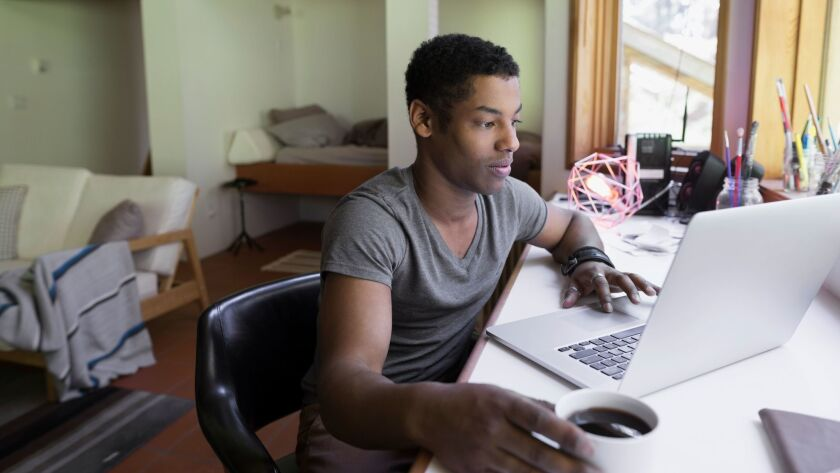 Man drinking coffee and working at laptop in home office