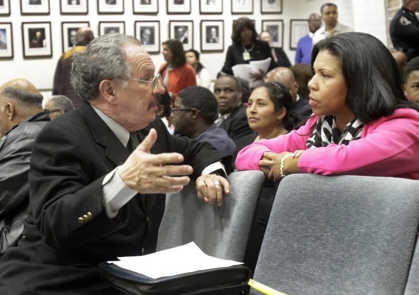 George McKenna, left, is seen talking with Corri Rabare of California Charter School Assoc. at the Los Angeles Board of Education district headquarter.