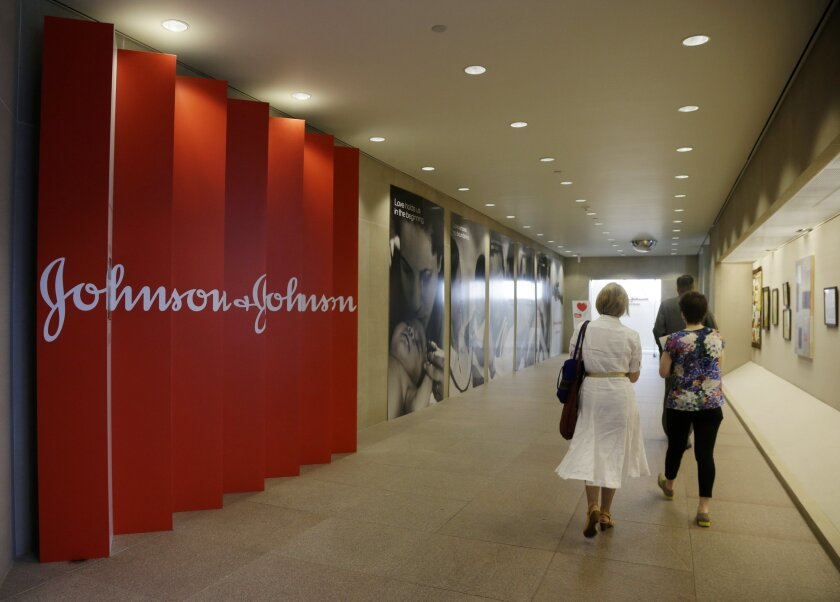 FILE - In this July 30, 2013, file photo, people walk along a corridor at the headquarters of Johnson & Johnson in New Brunswick, N.J. Johnson & Johnson is buying hair care products maker Vogue International. (AP Photo/Mel Evans, File)