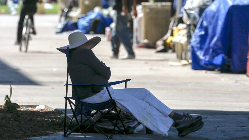 Homeless people gather near their campsites in the Santa Ana Civic Center Plaza.