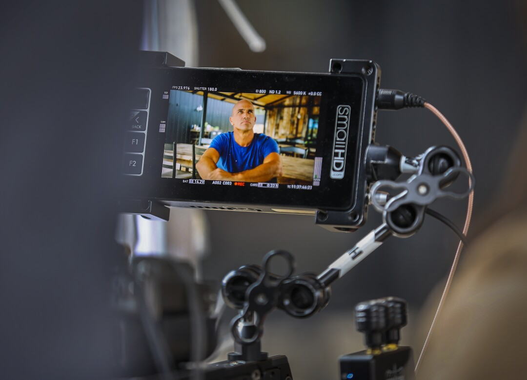 A video monitor shows Kelly Slater as he is interviewed on camera.