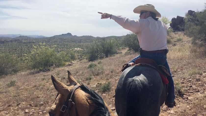 Head wrangler Paul Vance points out peaks surrounding the 20,000-acre ranch.