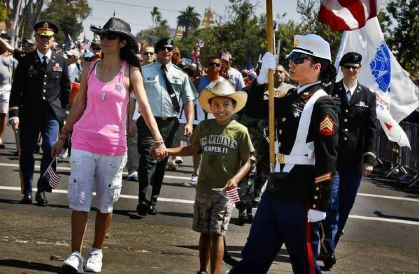 Kannon Cole, 7, watches his mother Marine Sgt. Bris Holland carry the flag at the beginning of San Diego's annual LGBT Pride parade. Holding his hand is her partner, Jaxs Jacquez.