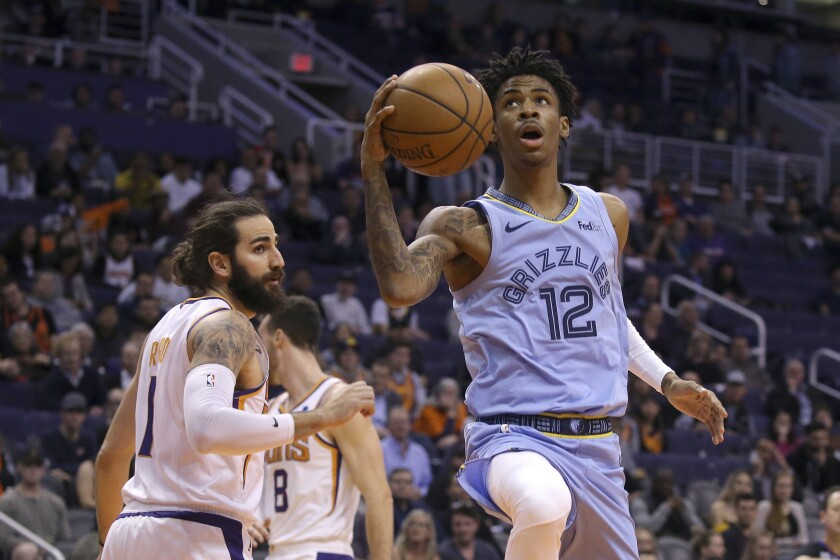 Memphis Grizzlies guard Ja Morant (12) drives past Phoenix Suns guard Ricky Rubio, left, during the first half of an NBA basketball game Wednesday, Dec. 11, 2019 in Phoenix. (AP Photo/Ross D. Franklin)