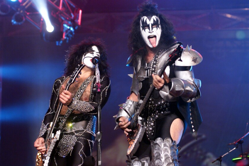 Two men with long, black hair play guitar in studded outfits and face paint.