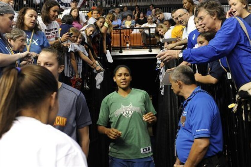 FILE - In this Aug. 16, 2011, file photo, fans reach out to Minnesota Lynx' Maya Moore, center, prior to a WNBA basketball game against the Connecticut Sun in Uncasville, Conn. Attendance and TV ratings are up for the WNBA, which is entering the final stretch of its 15th season. (AP Photo/Jessica Hill, File)
