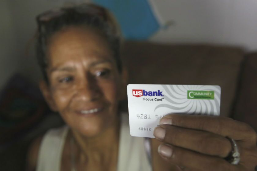 """Susie Garza displays a city-provided debit card she receives monthly through a trial program in Stockton.  She  is part of an experiment testing the impact of """"universal basic income."""""""