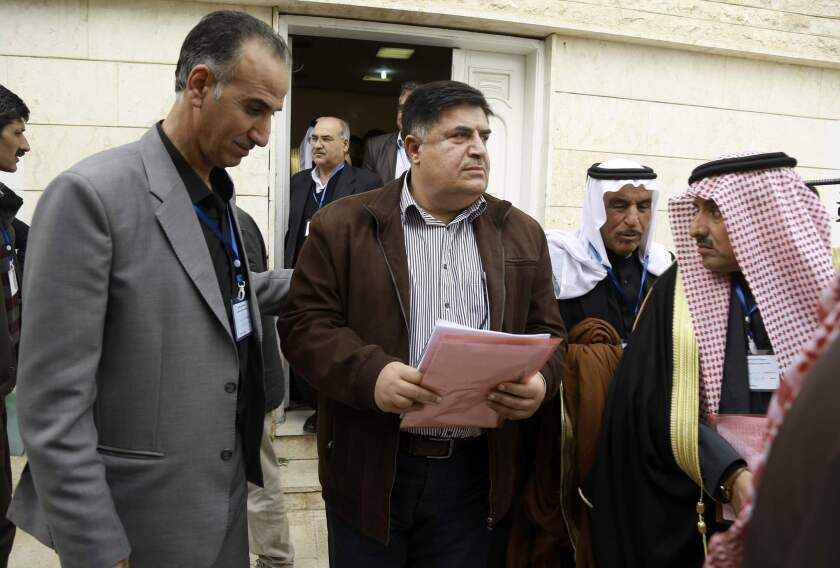 Amer Halloush, center, of the Syrian Democratic Council, the political branch of a Kurdish-Arab fighting force, leaves after a meeting of more than 150 delegates from Kurdish, Arab, Assyrian and other parties in Syria's northeastern Hassakeh province.