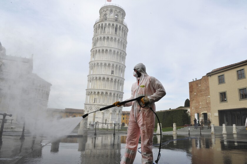 A worker carries out sanitation operations for the coronavirus emergency near the Tower of Pisa amid a devastating coronavirus outbreak.