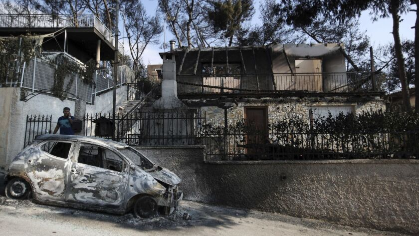 A man stands next to his burned house and car as he speaks on his cellphone in Mati, east of Athens,