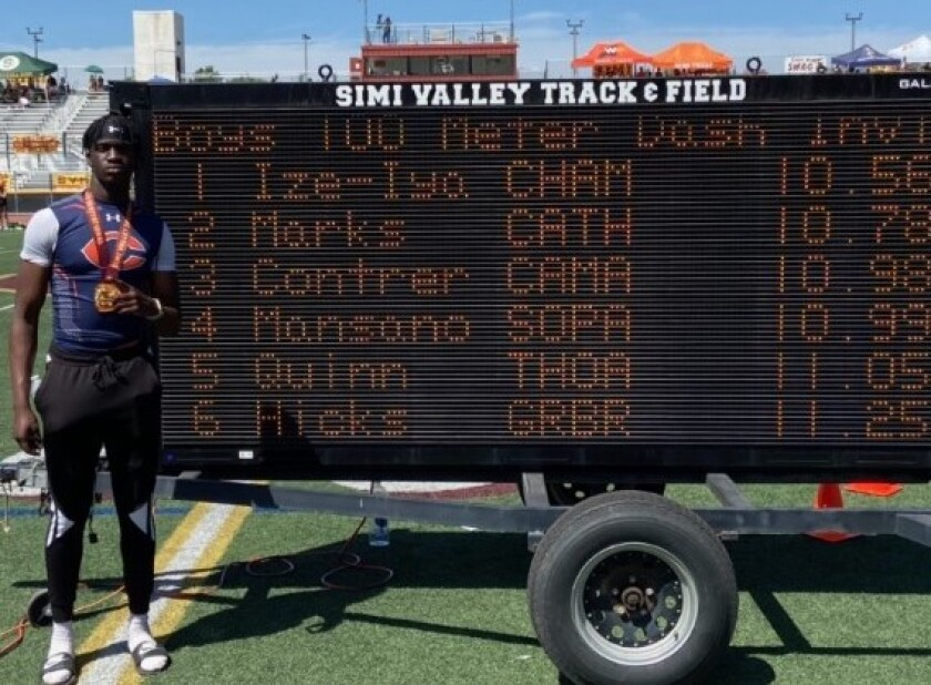 Junior Patrick Ize-Iyamu of Chaminade poses for a photo in front of the scoreboard showing his state-best 100-meter time.