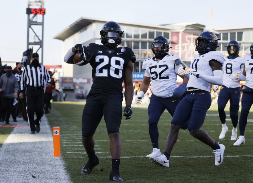Iowa State running back Breece Hall, left, runs in a touchdown as West Virginia defensive lineman Jalen Thornton, center, and cornerback Nicktroy Fortune, right, are late to the play during the first half of an NCAA college football game, Saturday, Dec. 5, 2020, in Ames, Iowa. (AP Photo/Matthew Putney)
