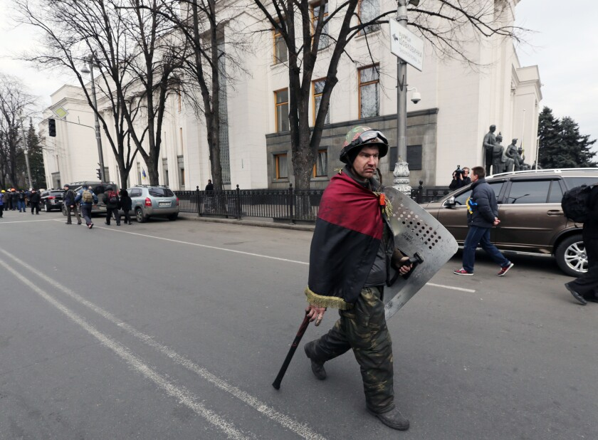 An opposition fighter wrapped in the nationalist red and black flag passes the parliament building in Kiev on Saturday.