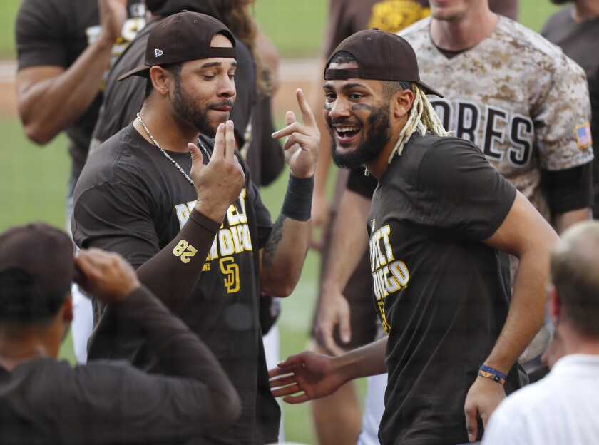 Tommy Pham and Fernando Tatis Jr. of the San Diego Padres celebrate after beating the Seattle Mariners and clinching a pla