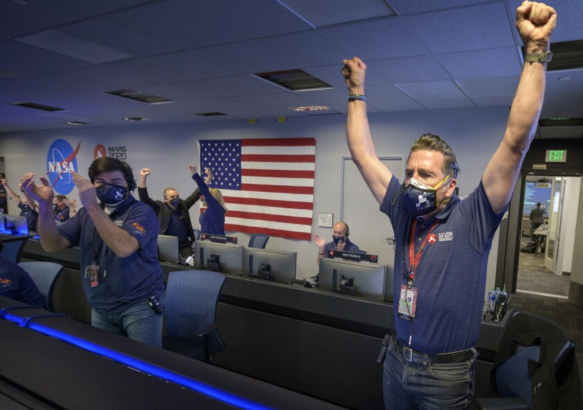 NASA staffers react in Pasadena after receiving confirmation a NASA rover successfully touched down on Mars.