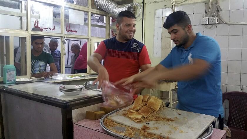 Qusai Taai, in red, prepares to serve a customer at his Kahi of Karrada cafe in Baghdad.