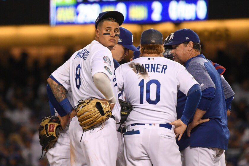 Manny Machado #8 of the Los Angeles Dodgers reacts on the mound against the Milwaukee Brewers during the eighth inning in Game Three of the National League Championship Series at Dodger Stadium on October 15, 2018 in Los Angeles, California.