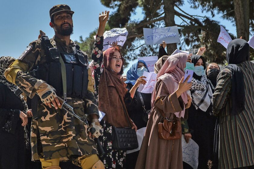 A Taliban fighter stands guard as Afghan women shout slogans