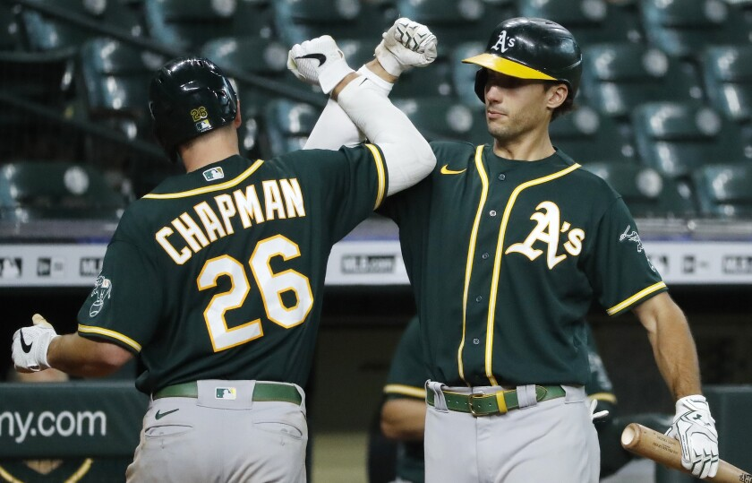 Oakland Athletics' Matt Chapman celebrates with Matt Olson after hitting a home run against the Houston Astros during the fourth inning of the second baseball game of a doubleheader Saturday, Aug. 29, 2020, in Houston. (Kevin M. Cox/The Galveston County Daily News via AP)